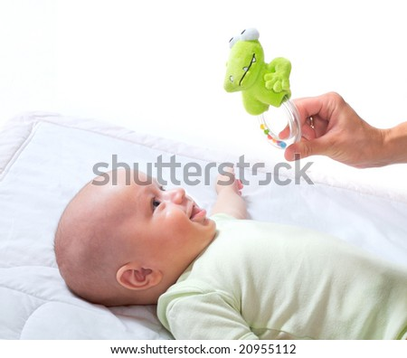 Mother plays with two months old baby girl. All toys visible on the photo are officially property released. - stock photo