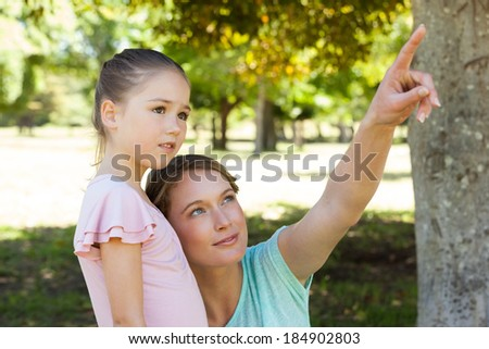 Mother pointing out at something besides daughter at the park - stock photo