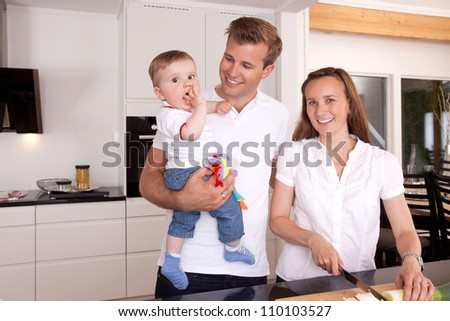 Mother preparing food with father and son standing beside smiling - stock photo