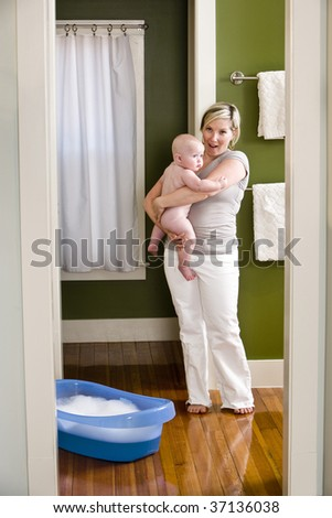 Mother preparing 7 month old baby for bath - stock photo