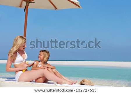 Mother Protecting Daughter With Sun Lotion On Beach Holiday - stock photo