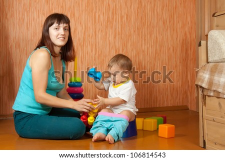 mother puts   baby on   potty at home - stock photo