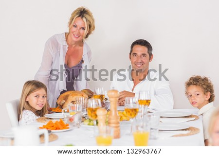 Mother putting a turkey on the table for dinner - stock photo