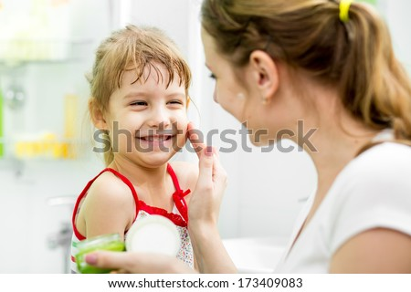 mother putting cream on her daughter's face in bathroom - stock photo