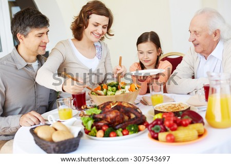 Mother putting salad on plate of daughter - stock photo