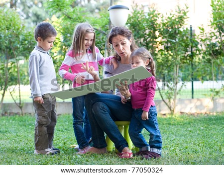 Mother reading a book to his sons. - stock photo
