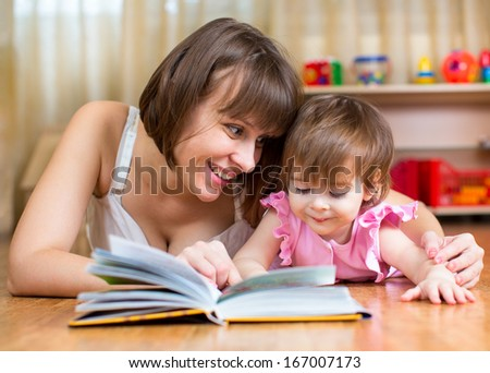 mother reading a book to kid at home - stock photo