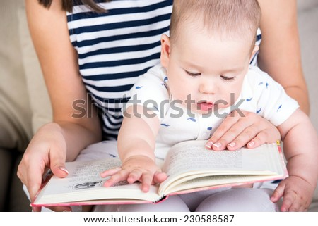 Mother reading a book to little baby son. - stock photo