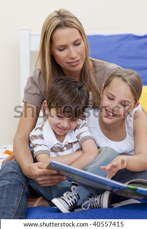 Mother reading a book with her daughter and son in bedroom - stock photo