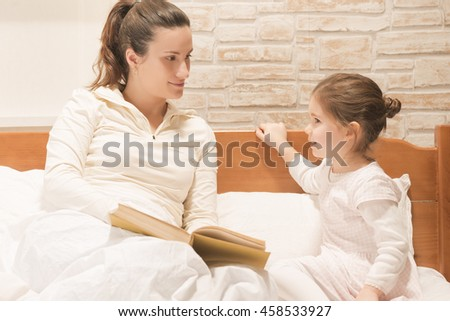 Mother reading bedtime stories to her beautiful little girl while sitting on the bed at home. Happy family concept - stock photo