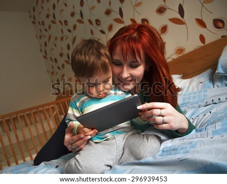 Mother reading bedtime stories to her son on digital tablet - stock photo