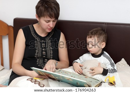 Mother reading book for her son in the bed - stock photo