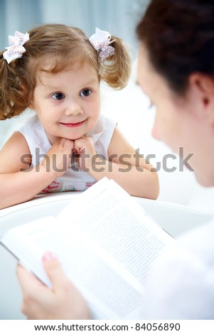 Mother reading book her cute little girl at home - stock photo