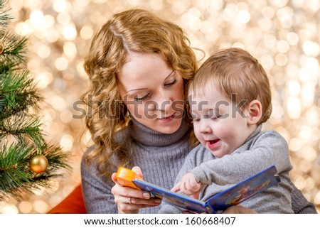 mother reading book to kid at Christmas tree - stock photo
