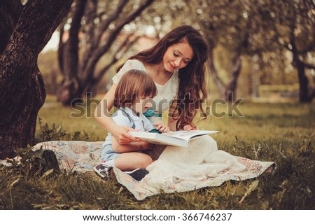 mother reading book to toddler son outdoor in spring garden. Family spending time together on picnic. Parent teaching kids on summer vacation. - stock photo