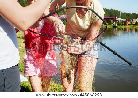 Mother removes a hook from a mouth of the caught carp at pond bank, two children stand near. - stock photo