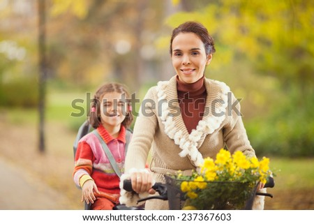 Mother riding a bicycle with her cute little daughter sitting on a back seat - stock photo