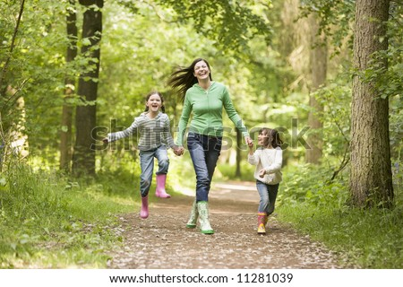 Mother running along woodland path with 2 childrren - stock photo
