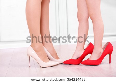 Mother's and daughter's legs in shoes - stock photo