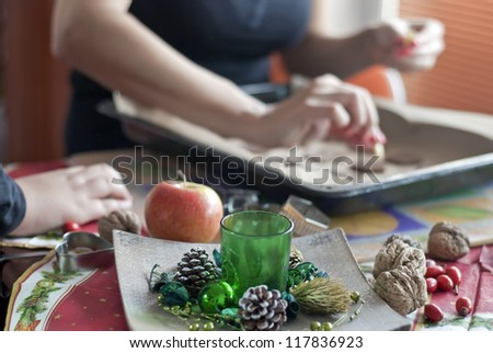 Mother's and son's hands going to the Christmas table - stock photo