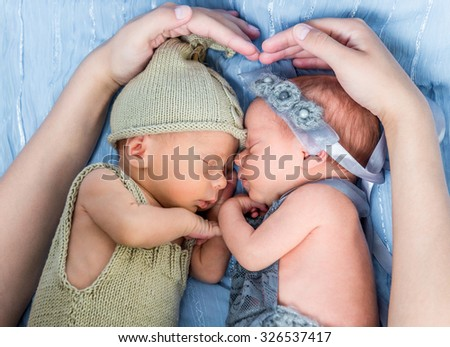 mother's arms wrapped around newborn twins  sleeping on a blue blanket - stock photo