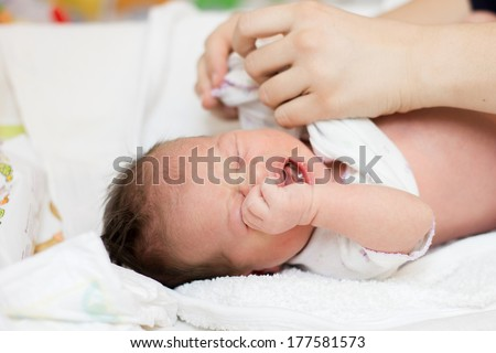 Mother's changing clothes of crying newborn baby. - stock photo