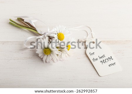 mother's day greeting with daisy flowers with name tag on wooden surface - stock photo
