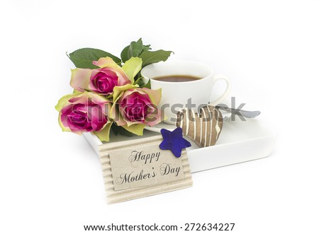 Mother's day morning tea with heart shape biscuit and roses with message card serving to mum in bed - stock photo