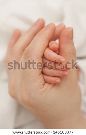 Mother's hand holding baby's hand - stock photo