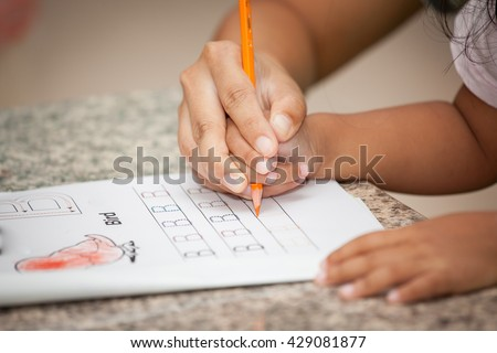 Mother's hand holding child hand writing her homework with crayon - stock photo