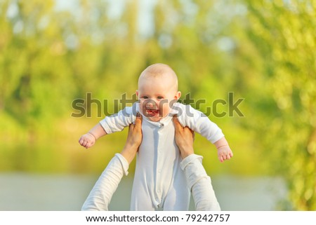 Mother's hands holding laughing adorable baby girl against sunny leaves - stock photo