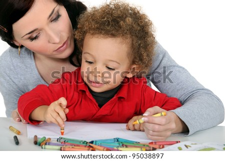 Mother sat with boy drawing - stock photo