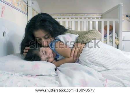 Mother saying goodnight and tucking her daughter into bed - stock photo