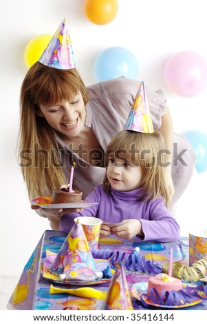 mother serving cake at childrens birthday party - stock photo