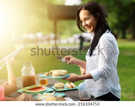 mother serving food at cookout barbecue in park - stock photo