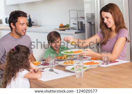 Mother serving vegetables to daughter at dinner in kitchen - stock photo