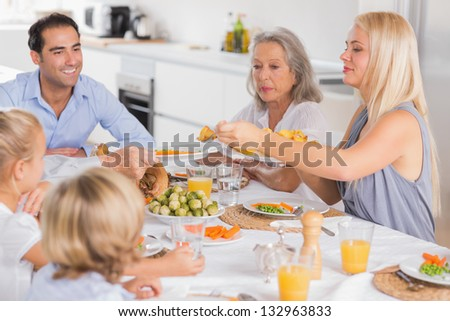Mother serving vegetables to her family - stock photo