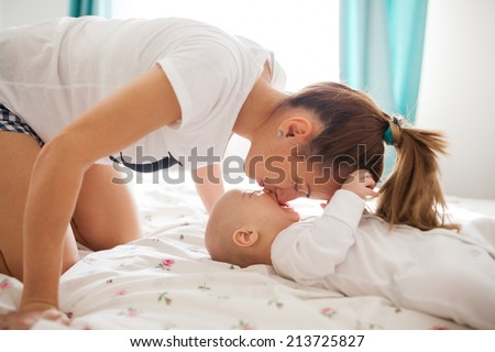 Mother showing affection towards little baby boy - stock photo