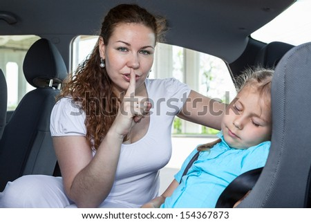 Mother showing shh gesture when child asleep in car - stock photo