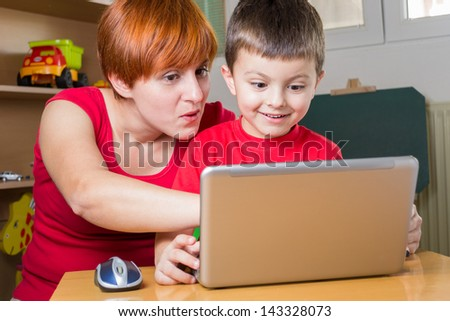 Mother showing something on the laptop to his son. He looks surprised - stock photo