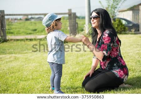 Mother showing to her toddler how to blowing dandelion - stock photo