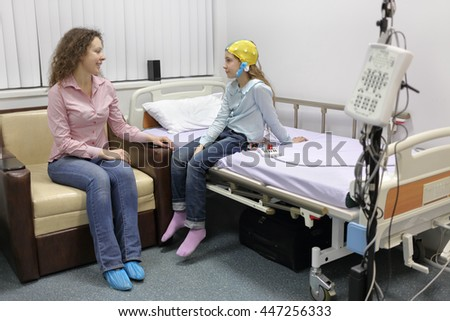mother sitting beside her daughter at withdrawal procedure of electroencephalogram, talking to her - stock photo