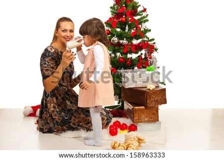 Mother sitting near Christms tree and her daughter drinking milk - stock photo
