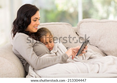 mother sitting on the couch with her sleeping daughter and using tablet computer - stock photo