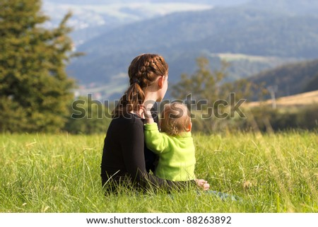 Mother sitting with child on meadow in mountains summer - stock photo