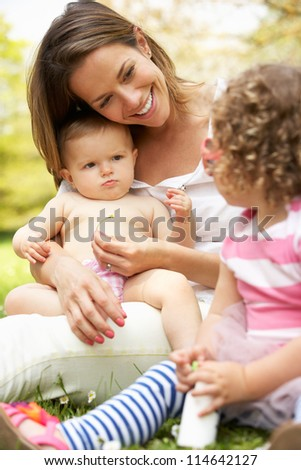 Mother Sitting With Daughters In Field Of Summer Flowers - stock photo