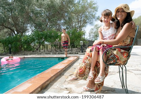 Mother sitting with young child in a holiday home with the brother and sister playing in the swimming pool during a sunny summer vacation, outdoors. Active family lifestyle enjoying the sun together. - stock photo