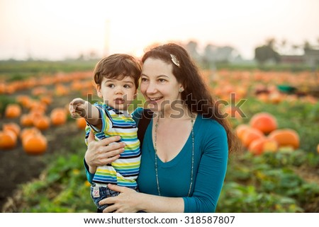 Mother son in a pumpkin patch - stock photo
