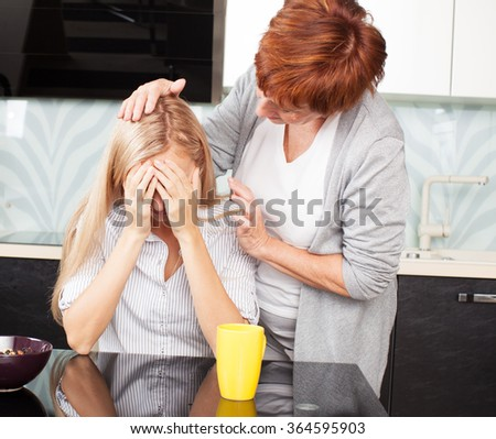 Mother soothes sad daughter. Mature woman calm young woman - stock photo