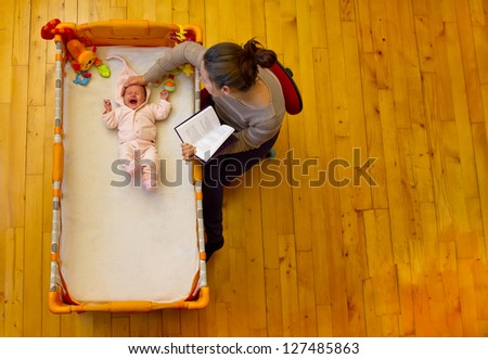 mother soothing her baby with reading and stroking - stock photo